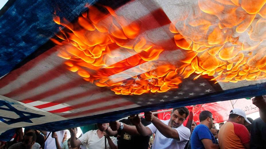 Manifestantes libaneses e palestinos atearam fogo a bandeiras americanas e israelenses durante manifestação contra os ataques aéreos israelenses na Faixa de Gaza, no sul da cidade de Sidon, no Líbano