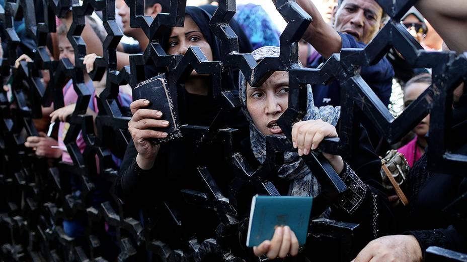 Palestinos seguram seus passaportes atrás de um portão na cidade de Rafah na Faixa de Gaza, equanto tentam entrar no Egito nesta quinta-feira (10)