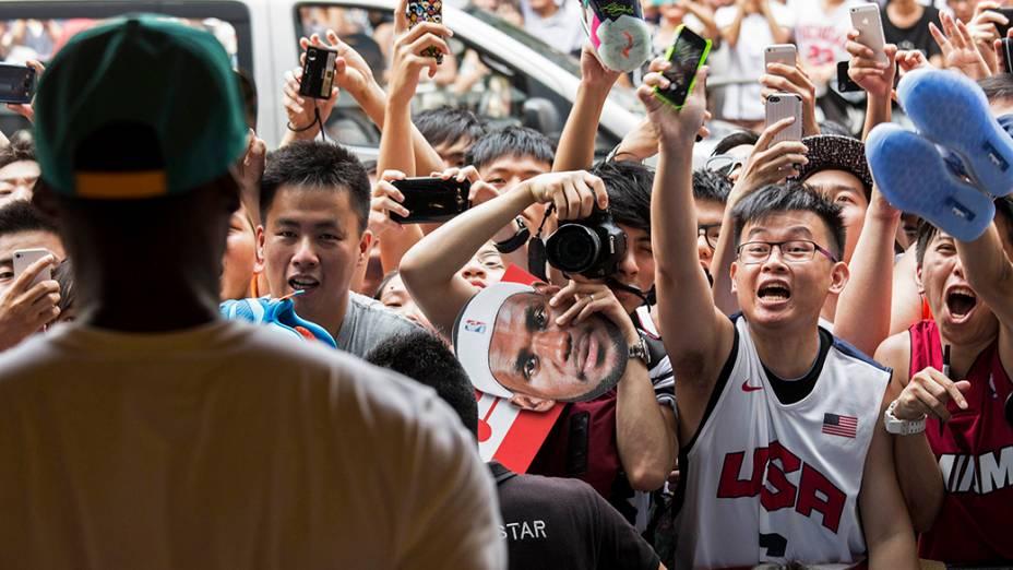 Fãs acename gritamcom a chegada do jogador de basquete da NBA, LeBron James,durante um evento promocional em Hong Kong, na China