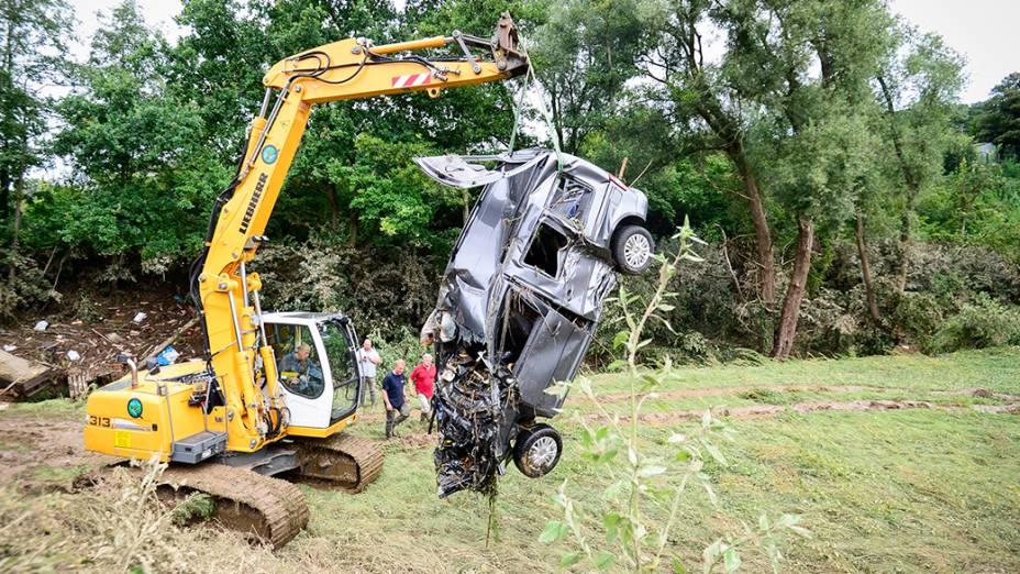 Na Bélgica, um guindaste remove um carro danificado na cidade deIttre -região oeste do país,depois quechuvas fortes causaram inundações nesta madrugada (30)
