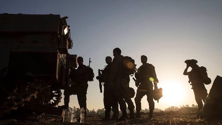 Soldados israelenses são vistos perto da fronteira com a Faixa de Gaza, da manhã desta quarta-feira (30). Segundo informaram asautoridades palestinas, pelo menos19 civis abrigados em uma escola nomaior campo de refugiados de Gaza foram mortos em ataques durante a madrugada; O conflito na região já ultrapassa três semanas