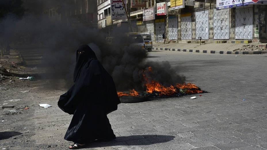 Uma mulher passa por vários pneus em chamas durante um protesto contra o aumento dos preços dos combustíveis, na cidade de Sanaa, no Iêmen