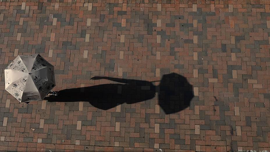 Pedestre se protege do sol durante um dia quente de verão em Hong Kong, na China. O clima de monções vem provocando altas temperaturas e fortes chuvas em toda a região