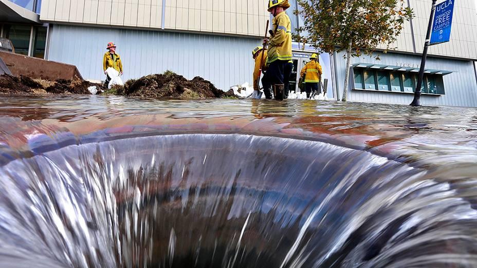 Bombeiros trabalham perto de um dreno aberto no campus da Universidade de Los Angeles, que ficou inundado após ruptura de uma adutora