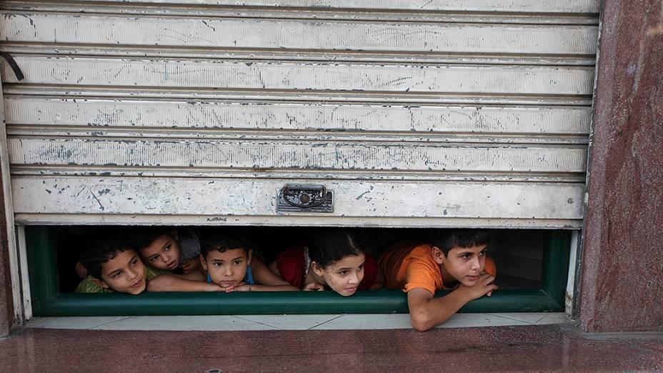 Crianças olham através da porta de uma loja as ambulâncias transportando feridos durante a ofensiva israelense, na Cidade de Gaza