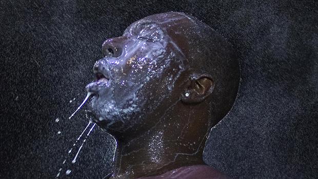 Homem é encharcado com leite após explosão de bomba de gás lacrimogéneo durante manifestação contra o assassinato de um jovem negro,em Ferguson