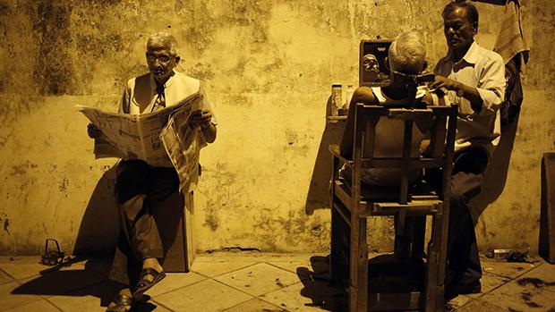 Homem aguarda para ser atendido em barbeiro de rua, em Nova Délhi, na Índia
