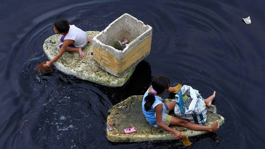Crianças usam pedaços de isopor como barquinhos para recolher lixo plástico na Baía de Manila, nas Filipinas. O material é vendido ao equivalente a pouco mais de R$ 0,04 por quilo<br>