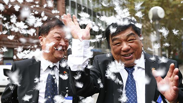 Executivos da empresa chinesa de processamento e manufatura Snowbird AG jogam plumas para o ar celebrando o lançamento da empresa na bolsa de valores em Frankfurt, na Alemanha. À direita, Yan Changzai (CEO), ao lado de Qiu Duoxiang (COO)
