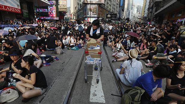 Estudante passa distribuindo alimentos e água para milhares de jovens que ocupam a via principal do distrito de compras em Hong Kong, em protesto exigindo democracia no território chinês