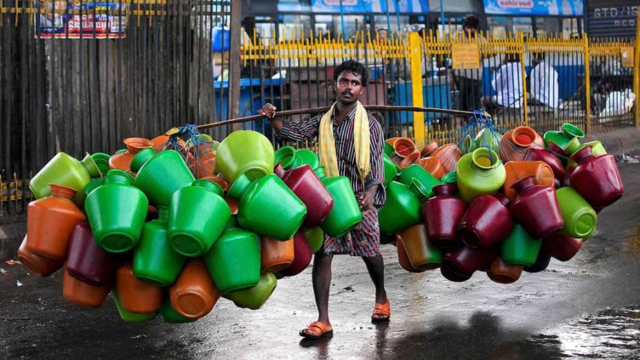 Vendedor carrega jarros de águaem um mercado na cidade indiana de Bangalore