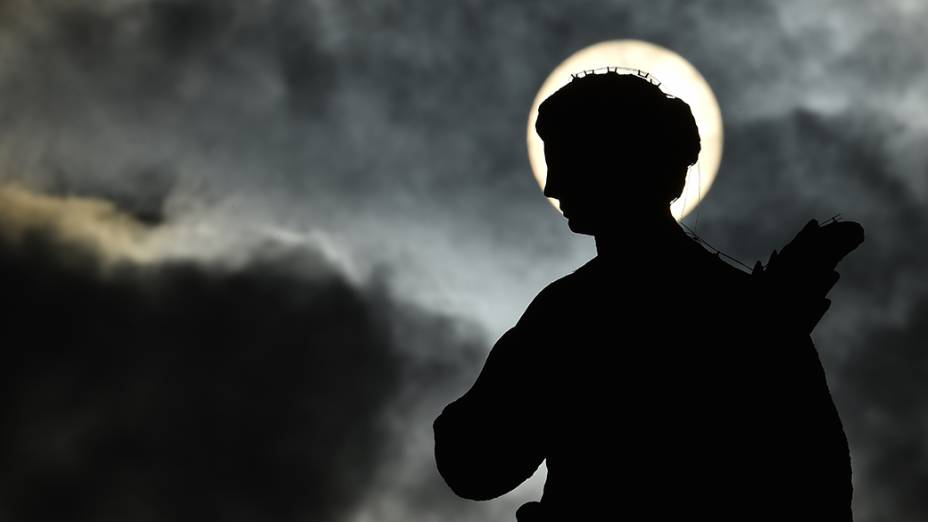 Imagem mostra a silhueta de uma estátua na praça de São Pedro, enquanto o sol nasce através das nuvens antes de uma audiência do papa Francisco, no Vaticano