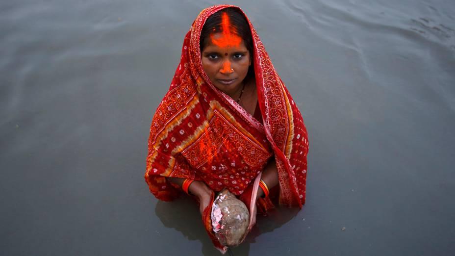 """No Nepal, mulher oferece orações ao sol durante o festival """"Chhat"""" no rio Bagmati em Kathmandu"""