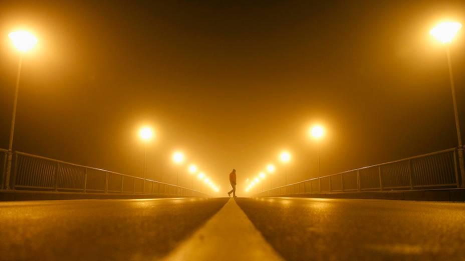 Homem fotografado durante a madrugada em uma rua de Zenica, na Bósnia e Herzegovina, em meio à densa neblina