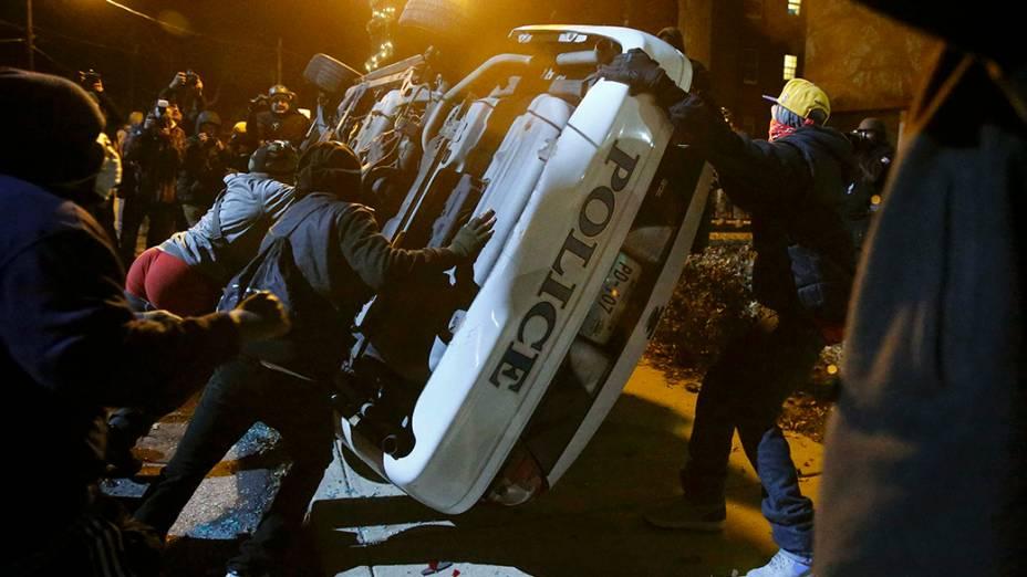 Nos Estados Unidos, manifestantes reviraram uma viatura policial em Ferguson, Missouri, na última segunda noite seguida de protestos após um júri inocentar o policial que matou um adolescente negro desarmado