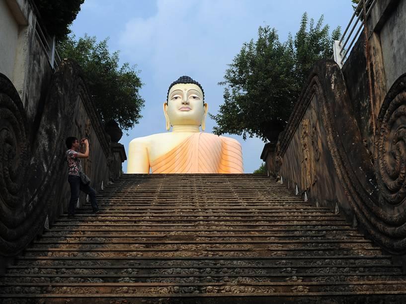 Turista tira foto no templo Kande Viharaya em Aluthgama, no Sri Lanka