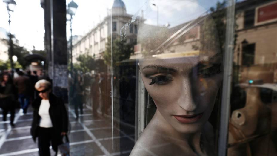 Mulher passa por comércio fechado o centro de Atenas, na Grécia