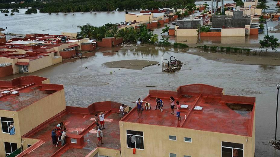 Moradores das colônias do porto de Acapulco permanecem nos telhados de suas casas inundadas. O governo mexicano confirmou hoje que já são 47 mortes, devido as chuvas e deslizamentos de terra no país, causada pelo furacão Ingrid e a tempestade Manuel