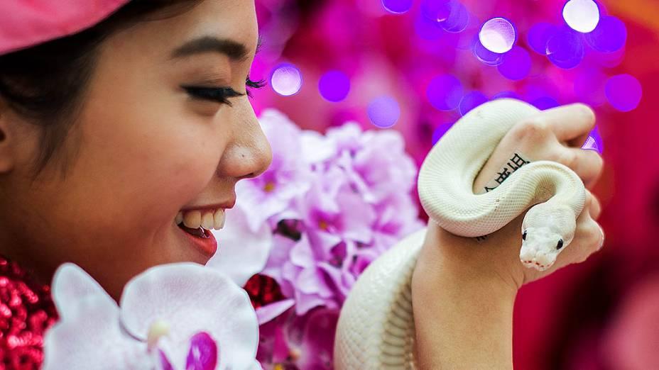 Modelo segura uma cobra durante uma exposição de cobras para promover a responsabilidade na venda e pose desses animais em Hong Kong na China
