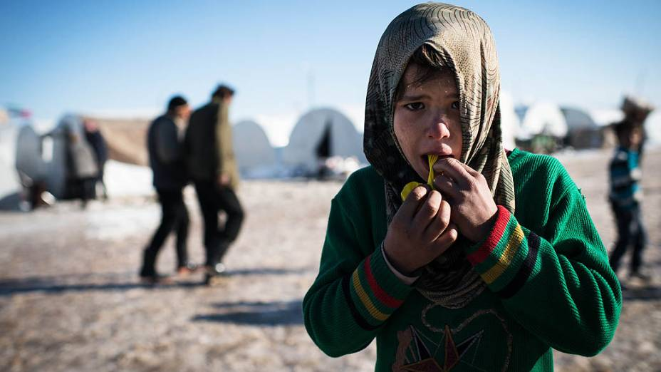 Criança síria brinca em campo de refugiados na fronteira entre Turquia e Síria, próximo à cidade de Azaz
