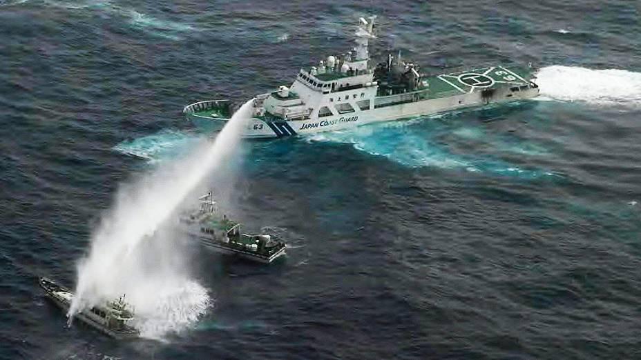 Navio da Guarda Costeira japonesa joga jato de água em barco de pesca, onde ativistas taiwaneses estvam a bordo no Mar da China Oriental