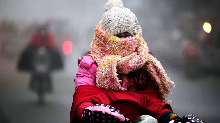 Uma mulher se protege do frio em Haozhou, província de Anhui, na China