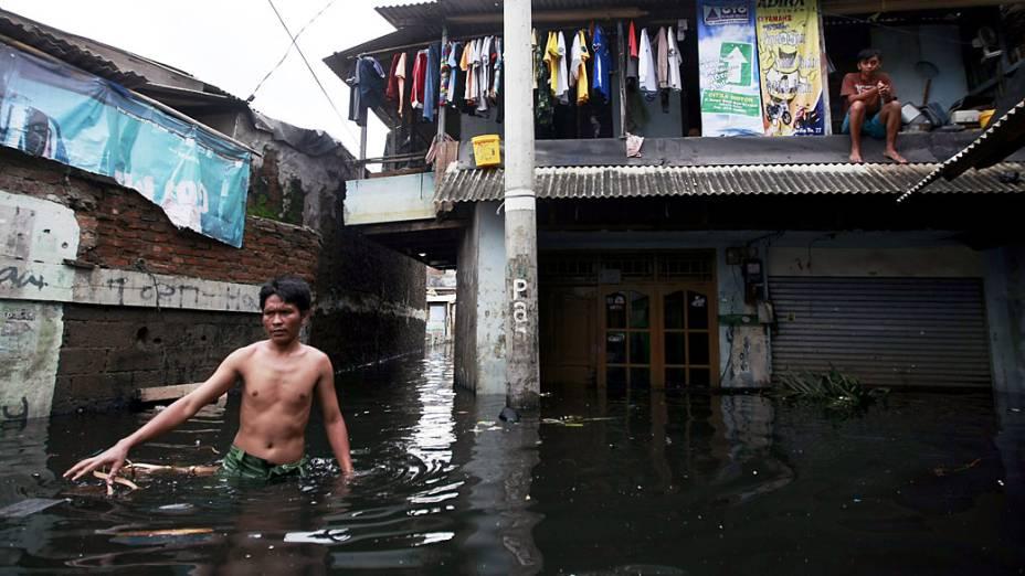 Vítima de enchente caminha em rua inundada em Jacarta, Indonésia