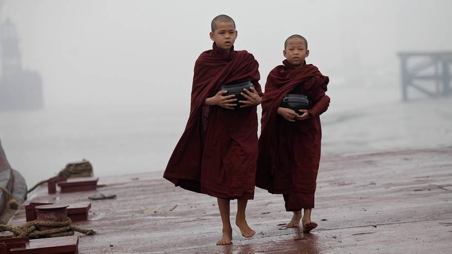 Jovens budistas caminham nas margens do rio durante manhã de forte névoa em Yangon (Mianmar)