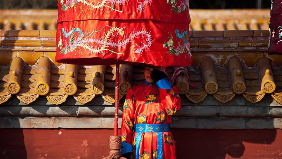 Menino se protege do sol próximo a um templo em Pequim (China), nesta sexta-feira (8). O país se prepara para receber o Ano-Novo lunar, em 10 de fevereiro
