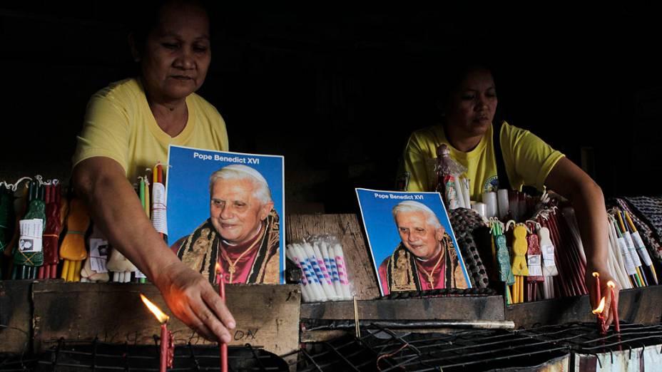 Moradores exibem imagens do Papa Bento XVI em frente de igreja católica em Antipolo, nas Filipinas