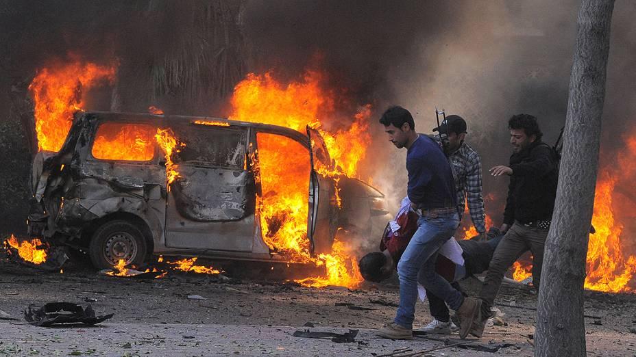 Guardas de segurança sírios carregam um corpo passando por carros em chamas no centro de Damasco, na Síria. Pelo menos 31 morreram na explosão de carro-bomba contra a sede do partido do ditador sírio, Bashar Assad