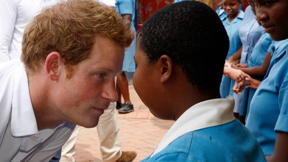 O príncipe britânico Harry conversa com criança de escola para deficientes visuais durante visita a Maseru, capital de Lesoto