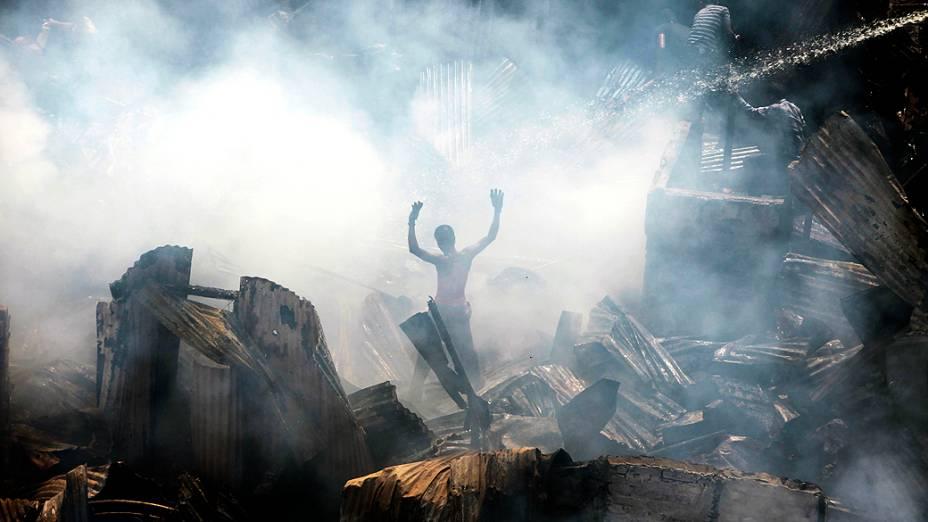 Moradores tentam controlar um incêndio em uma favela em Dhaka, em Bangladesh