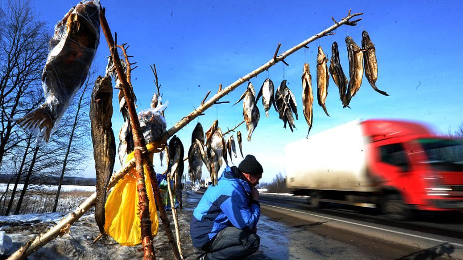 Vendedor de peixes aguarda à beira de uma rodovia em Lapichi, vila bielorrussa a 95 km de Minsk