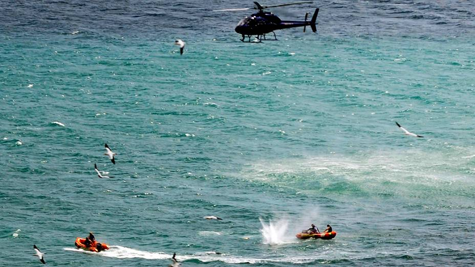 Policiais em barco inflável disparam tiros na água durante tentativa de acertar tubarão que matou um banhista na praia de Muriwai, em Aucklandna Nova Zelândia