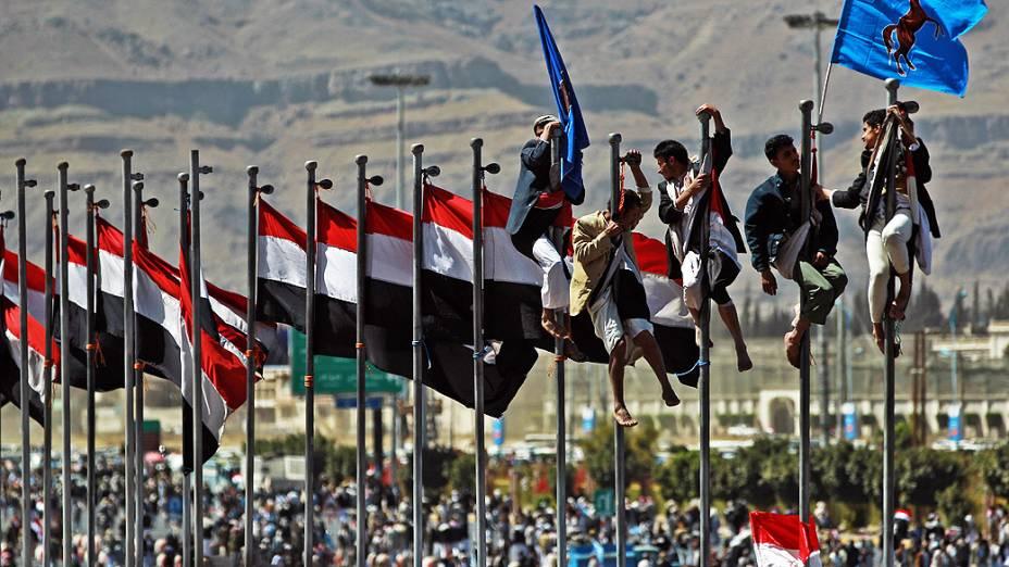 Iemenitas escalam postes em área de Sanaa, durante manifestação para comemorar o aniversário da renúncia do presidente Ali Abdullah Saleh