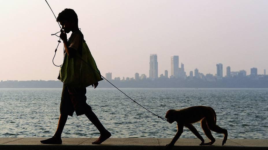 Garoto se prepara para fazer um show de acrobacias com seu macaco às margens do mar da Árabia, em Mumbai (Índia)