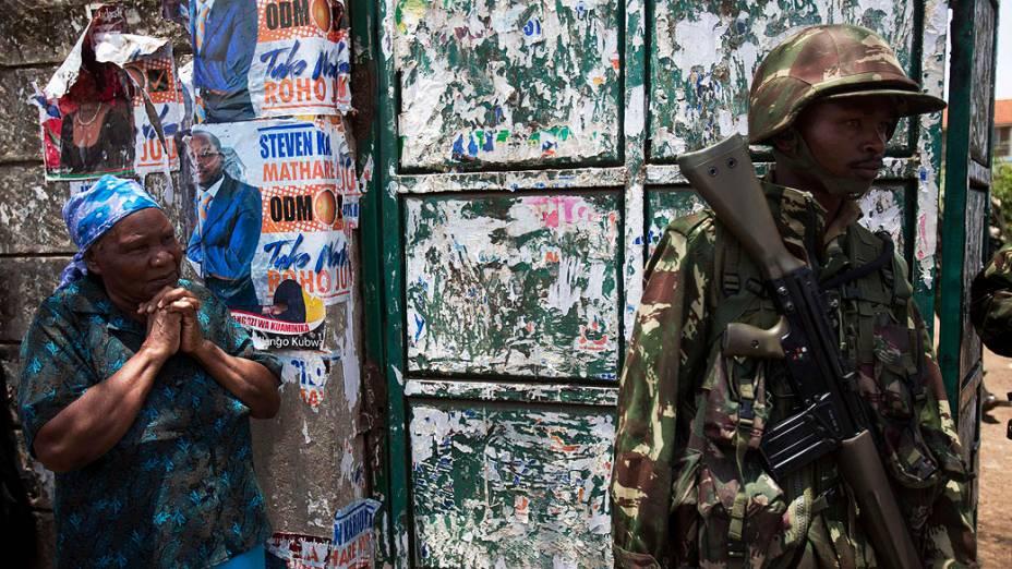 Mulher espera do lado de fora de um centro de contagem de votos, em Nairóbi, Quênia