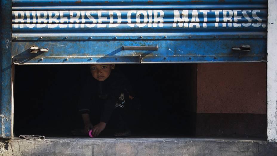 Criança olha através da porta de uma loja durante greve geral em Katmandu, Nepal