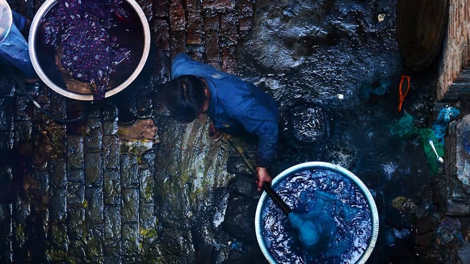 Trabalhador tinge tecidos em fábrica em Lahore, Paquistão