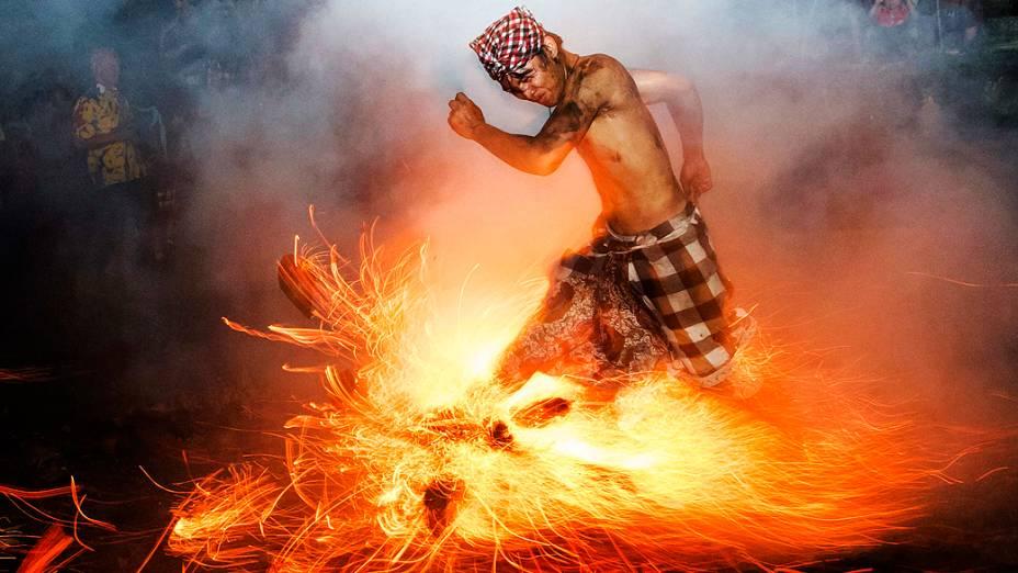 Homem chuta uma fogueira durante o ritual Perang Api, à frente do Nyepi, data do Ano Novo hindu em Bali, Indonésia, conhecido como dia do silêncio, quando hindus da ilha meditam e jejuam