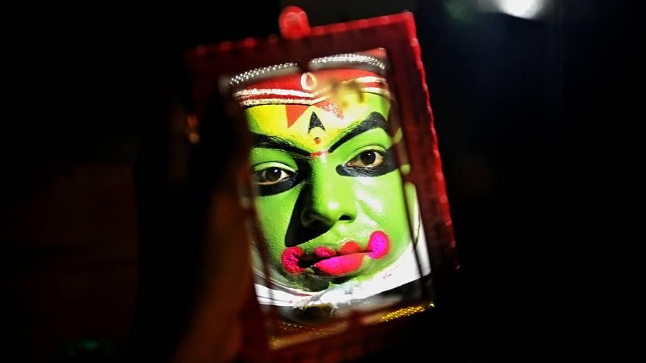 Um artista tradicional coloca a maquiagem antes de um evento, na Índia