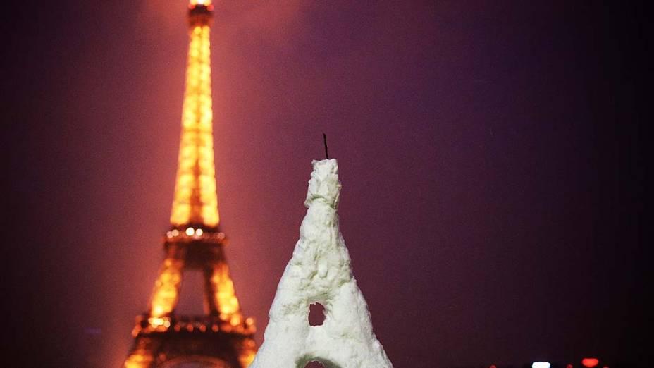 Uma Torre Eiffel feita na neve é fotografada em frente à Torre Eiffel em Paris. Tempestades de neve inesperadas para a época atingiram a Europa, incluindo Espanha e França