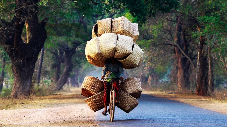 Mulher carrega diversas cestas para vender em um mercado perto da montanha Lapdaung, em Mianmar