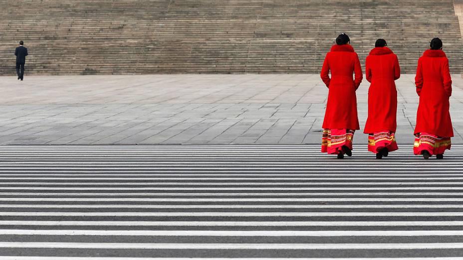 Funcionárias de um hotel caminham na Praça Tiananmen, em Pequim, perto do Grande Salão do Povo, onde ocorre a quarta reunião de plenário do Congresso Nacional do Povo (NPC)
