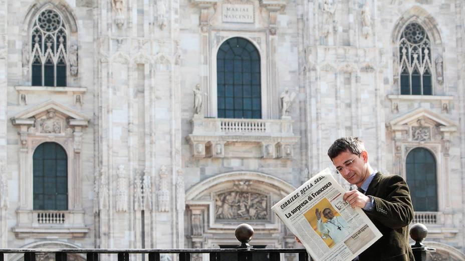 Homem lê um jornal italiano que mostra o Papa recém-eleito, Francisco I, na praça Duomo, centro de Milão