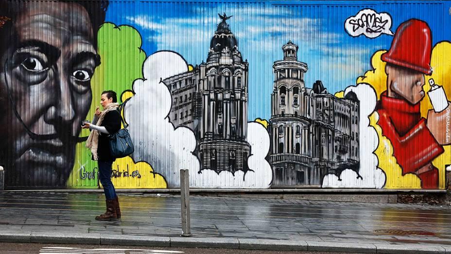 Mulher fuma em frente à um mural com grafites de arte em Madrid, na Espanha