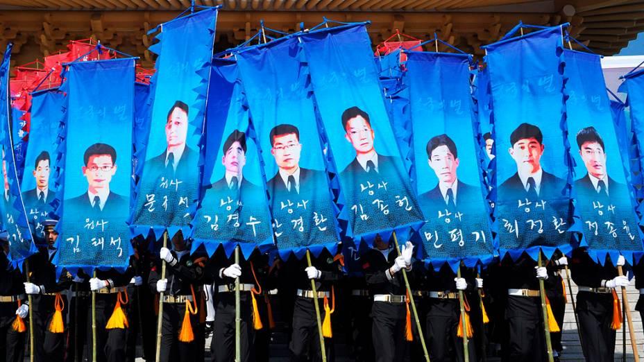 Guardas de Honra sul-coreanos seguram bandeiras com imagens dos marinheiros que morreram no naufrágio de um navio em Seul, durante evento que marca o terceiro aniversário do acidente, no cemitério nacional em Daejeon