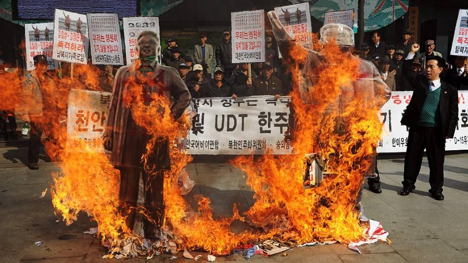 Ativistas sul-coreanos queimam dois retratos de antigos líderes norte-coreanos, Kim Il-Sung e Kim Jong-Il, durante manifestação contra a Coreia do Norte