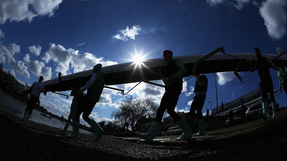Equipe de canoagem de Cambridge leva barco para a água durante uma excursão de treinamento no rio Tamisa, em Londres, Inglaterra